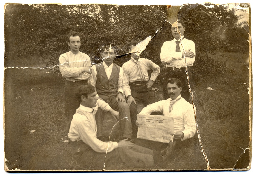 US 65 - New York, c 1900s, A group of workers in shirtsleeves sit and stand on the grass. One reads the Forward.jpg